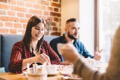 Couples heureux se reposant dans un restaurant, mangeant Image libre de droits