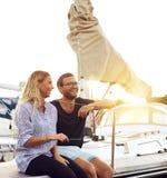 Couples heureux se reposant devant un bateau à voile Images stock