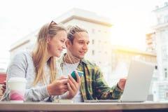 Couples heureux se reposant en café avec l'ordinateur portable et discutant des plans ensemble Photographie stock
