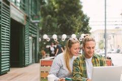 Couples heureux se reposant en café de rue ensemble et à l'aide de l'ordinateur portable Images stock