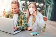 Couples heureux se reposant en café de rue ensemble et à l'aide de l'ordinateur portable, boire de femme Photo libre de droits