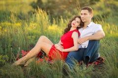 Couples heureux se reposant sur l'herbe en parc Photo stock