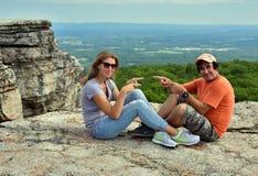 Couples heureux se reposant sur la roche au parc d'état de Minnewaska Images stock