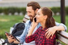 Couples heureux se reposant sur le banc Image libre de droits