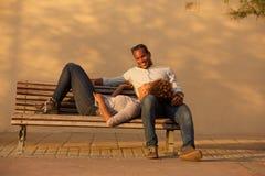 Couples heureux se reposant sur le banc de parc dehors photos libres de droits