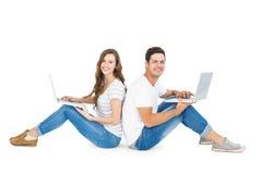 Couples heureux se reposant sur le plancher de nouveau au dos utilisant l'ordinateur portable Image libre de droits