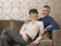 Couples heureux se reposant sur le sofa image stock