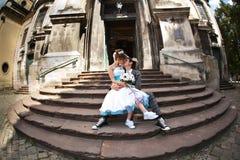 Couples heureux se reposant sur les escaliers et embrassant sur le fond vieux Photos libres de droits