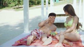 Couples heureux se reposant sur les verres de plage, de parler et tinter avec des cocktails banque de vidéos
