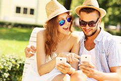 Couples heureux se reposant sur un banc avec des smartphones Photo stock