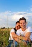 Couples heureux se reposant sur un pré ou un grainfield Photographie stock