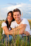 Couples heureux se reposant sur un pré ou un grainfield Photographie stock libre de droits