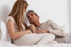 Couples heureux se situant dans le lit Photo libre de droits