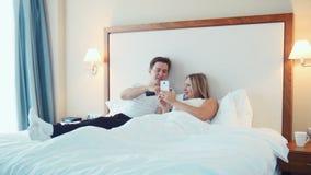 Couples heureux se situant dans le lit observant la TV et le smartphone d'utilisation clips vidéos