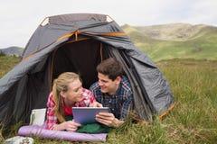 Couples heureux se situant dans leur tente et à l'aide du comprimé numérique Image libre de droits