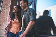 Couples heureux se tenant près de la fenêtre et examinant la distance photos stock
