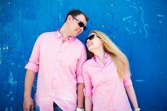 Couples heureux se tenant sur le fond bleu de mur Photographie stock