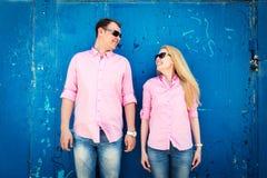 Couples heureux se tenant sur le fond bleu de mur Photos stock