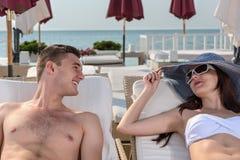 Couples heureux se trouvant sur des chaises longues à la plage Photographie stock libre de droits