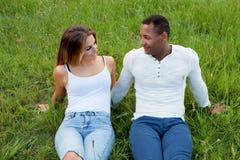 Couples heureux se trouvant sur l'herbe dans le domaine image libre de droits