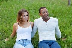 Couples heureux se trouvant sur l'herbe dans le domaine Photos libres de droits