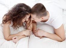 Couples heureux se trouvant sur le lit regardant l'un l'autre image stock