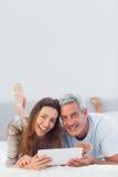 Couples heureux se trouvant sur le lit utilisant leur PC de comprimé photo stock
