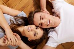 Couples heureux se trouvant sur le plancher Photo stock