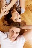 Couples heureux se trouvant sur le plancher Photos libres de droits