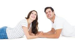 Couples heureux se trouvant sur le plancher recherchant photographie stock
