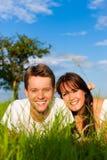 Couples heureux se trouvant sur un pré Photos libres de droits
