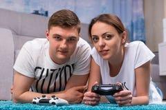 Couples heureux se trouvant sur une couverture et jouant des jeux vidéo Photos stock