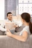 Couples heureux souriant à l'un l'autre s'asseyant sur le sofa Photos stock