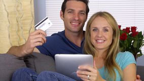 Couples heureux souriant avec la carte de crédit et le comprimé Photos libres de droits