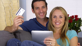 Couples heureux souriant avec la carte de crédit et le comprimé Photographie stock libre de droits