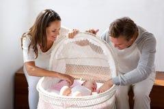 Couples heureux souriant avec le bébé dans le berceau Photos libres de droits