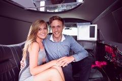 Couples heureux souriant dans la limousine Images stock