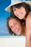 Couples heureux souriant sur la plage Photographie stock libre de droits