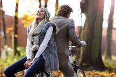 Couples heureux sur des vélos dans la forêt pendant le temps de chute Image libre de droits