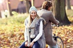 Couples heureux sur des vélos dans la forêt pendant le temps de chute Image stock