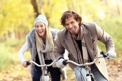 Couples heureux sur des vélos dans la forêt pendant le temps de chute Photos stock