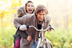 Couples heureux sur des vélos dans la forêt pendant le temps de chute Images libres de droits