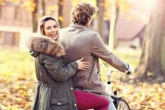 Couples heureux sur des vélos dans la forêt pendant le temps de chute Images stock
