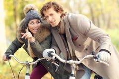 Couples heureux sur des vélos dans la forêt pendant le temps de chute Photo libre de droits