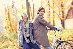 Couples heureux sur des vélos dans la forêt pendant le temps de chute Photo stock