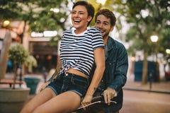 Couples heureux sur la bicyclette dans la ville Images stock