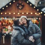 Couples heureux sur la place de ville décorée pour un marke de Noël Image stock