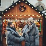 Couples heureux sur la place de ville décorée pour un marke de Noël Images stock