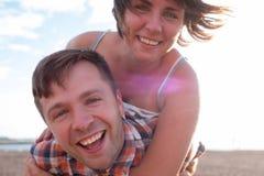 Couples heureux sur la plage La fille tient son ami dessus de retour Images libres de droits