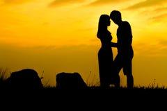 Couples heureux sur la roche de coucher du soleil - silhouette Photos libres de droits